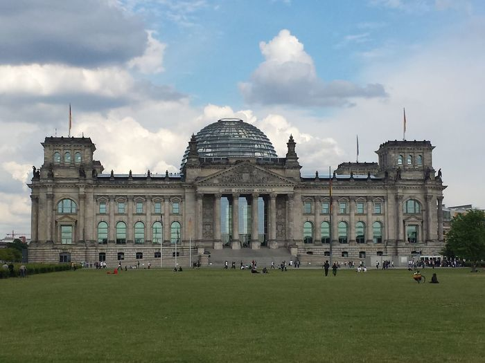 Tourist visiting the reichstag against sky