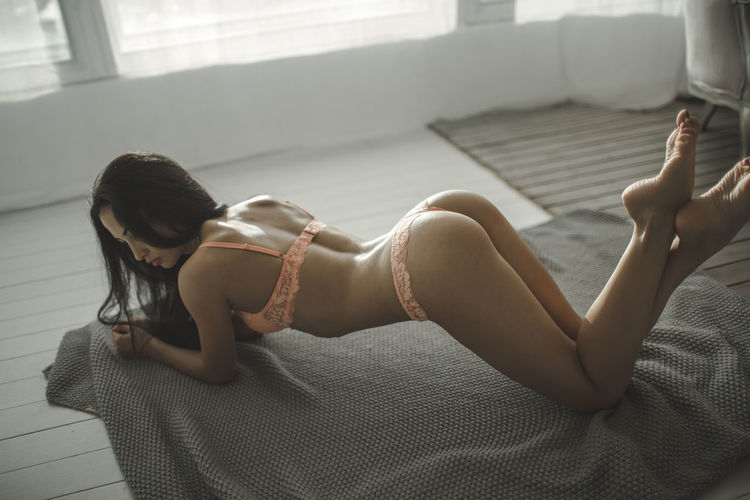 High angle view of sensuous female model wearing lingerie while lying at home