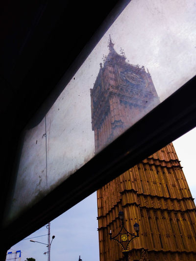 Low angle view of building seen through window