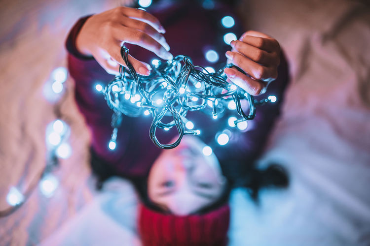 it's beginning to look alot like christmas.🎄🎉 Young woman wearing red sweater looking lights in hand and blurry background. People Real People Men Women Portrait Christmas Christmas Lights Christmas Decoration Finger Headshot Indoors  Adult Close-up Holding Front View Lifestyles Young Adult Selective Focus Leisure Activity Focus On Foreground Human Body Part Midsection Christmas Ornament
