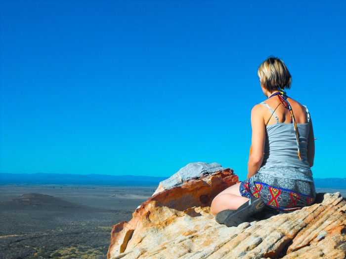 Rear view of woman sitting on rock against clear blue sky