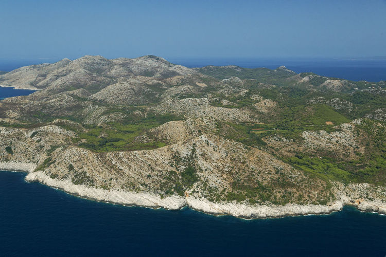 Aerial view of sea and mountains against clear blue sky