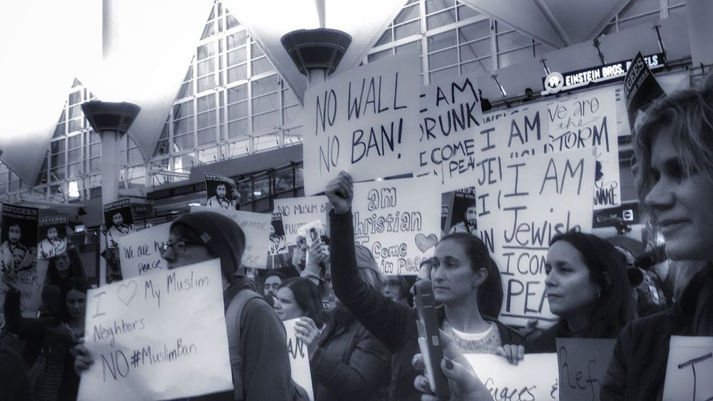 Protesting against the ban on refugees Real People DenverInternationalAirport Welcomehomeomar Muslimandproud NOTMYPRESIDENT Denver,CO Denver Colorado