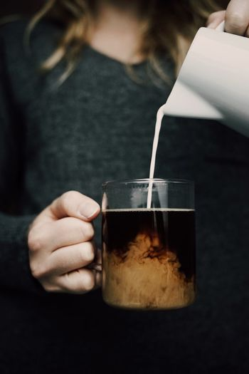 Midsection Of Woman Pouring Milk In Coffee
