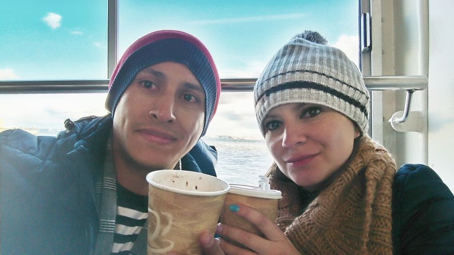 Portrait of friends wearing warm clothing while holding coffee cups against window in ship
