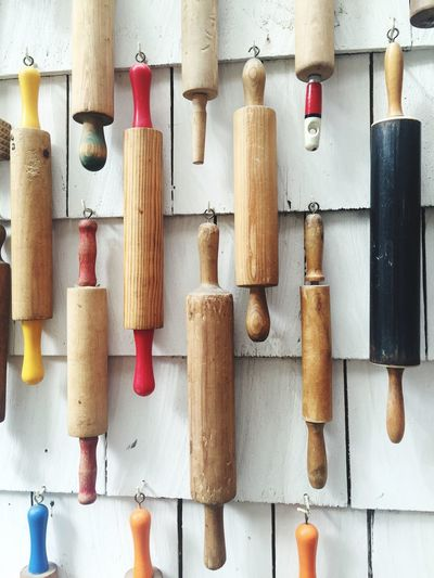 Close-up of wooden rolling pins hanging against wall