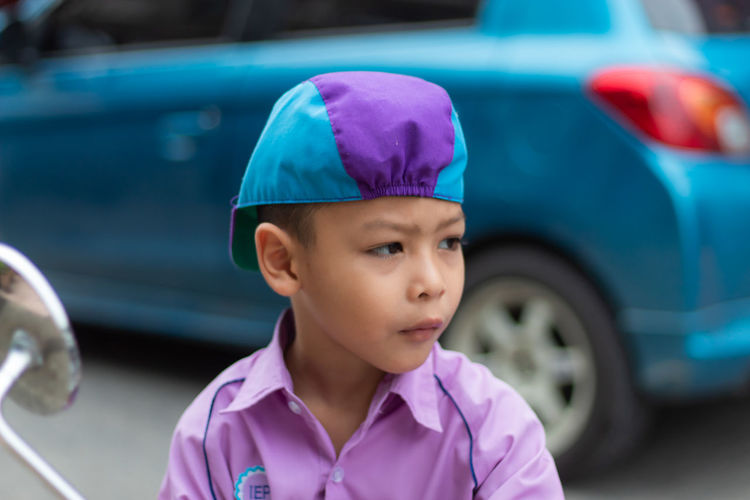 Cute boy looking away while standing against car on road
