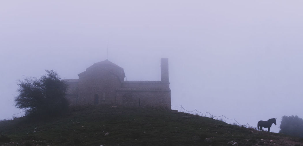 Building against sky during foggy weather