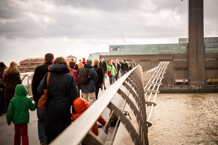 Group of people crossing the Millennium Bridge in London, UK. Group Of People Crowd Architecture Real People Built Structure Bridge - Man Made Structure River Water London Overcast Cloudy Rear View Bridge United Kingdom Uk Large Group Of People Building Exterior Millenium Bridge Footbridge Pedestrian Walkway Outdoors