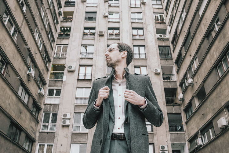 Low angle view of man looking away while standing against building in city