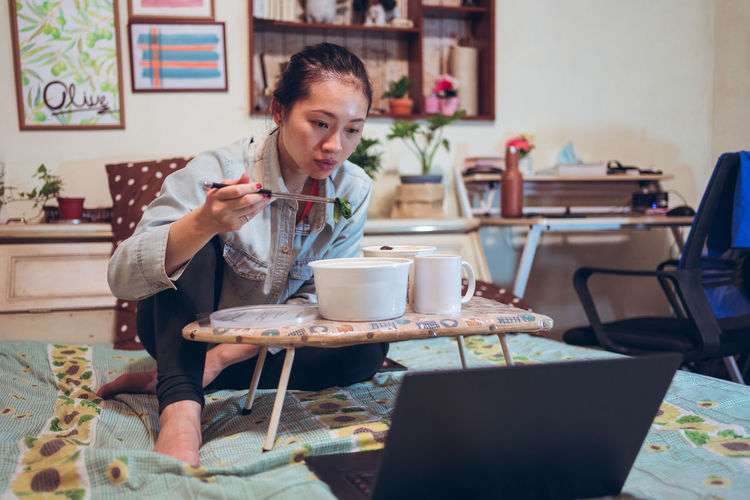 Woman using laptop while sitting at table