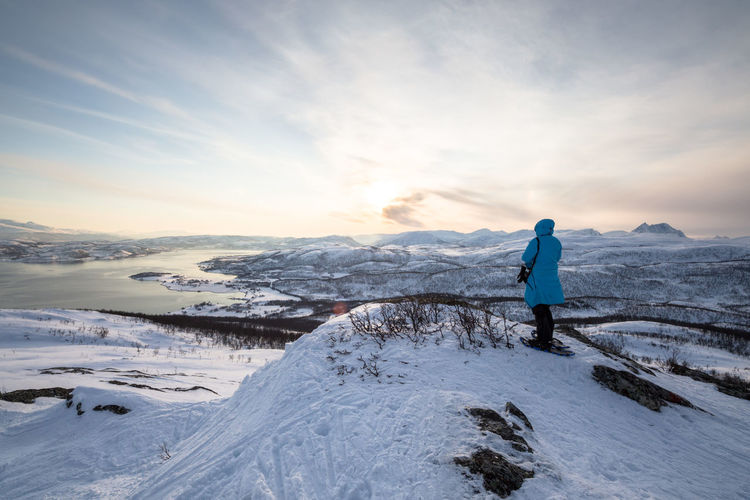 Adventure Beauty In Nature Cloud - Sky Cold Temperature Full Length Hiking Landscape Leisure Activity Mountain Nature Northern Norway Norway One Person Outdoors People Rear View Sky Snow Sunset Tourism Travel Travel Destinations Vacations Warm Clothing Winter