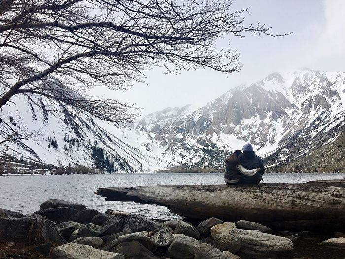 Couple sitting on rock by lake against sky during winter