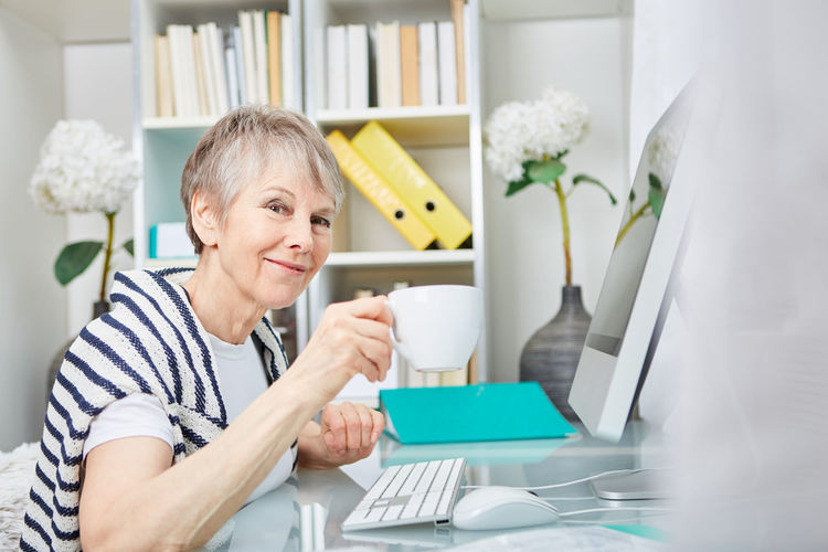 Portrait of smiling senior woman drinking coffee by desktop pc on desk at home