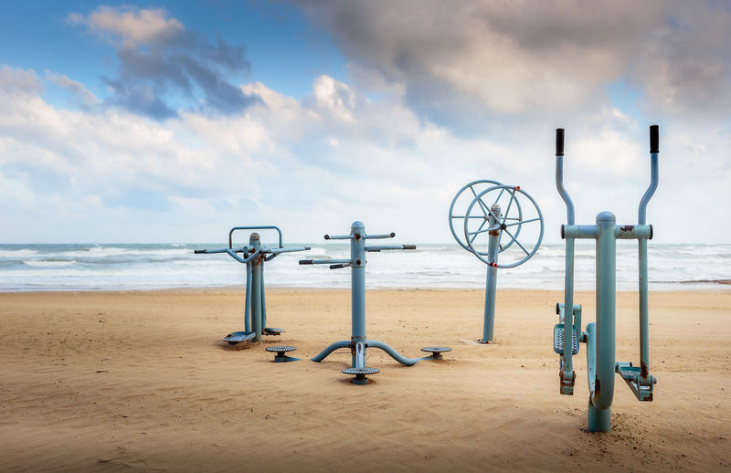 View of fitness equipment on sandy beach against cloudy sky