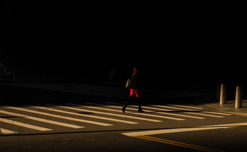 Woman Crossing Road In City