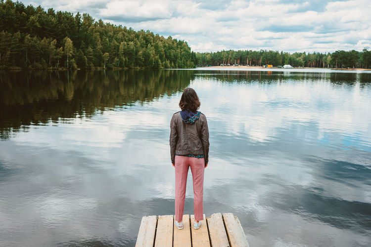 Top view of a lonely girl standing on the pier of a forest lake