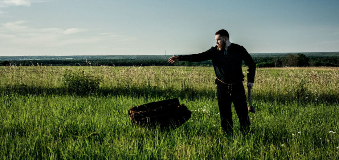 Man with axe standing on field against sky