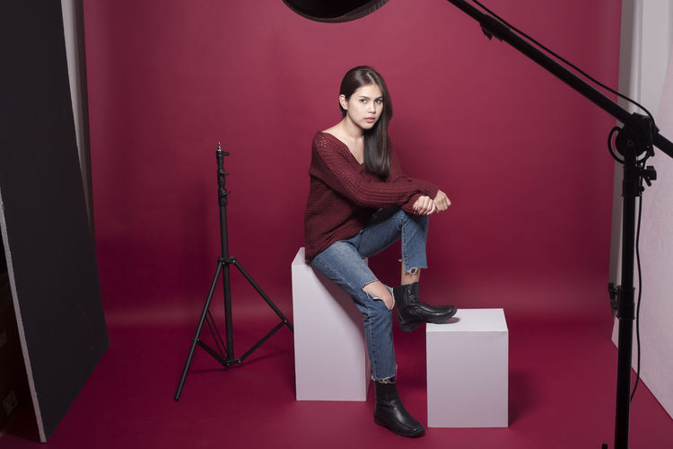 Portrait of woman with tripod camera and lighting equipment sitting in studio