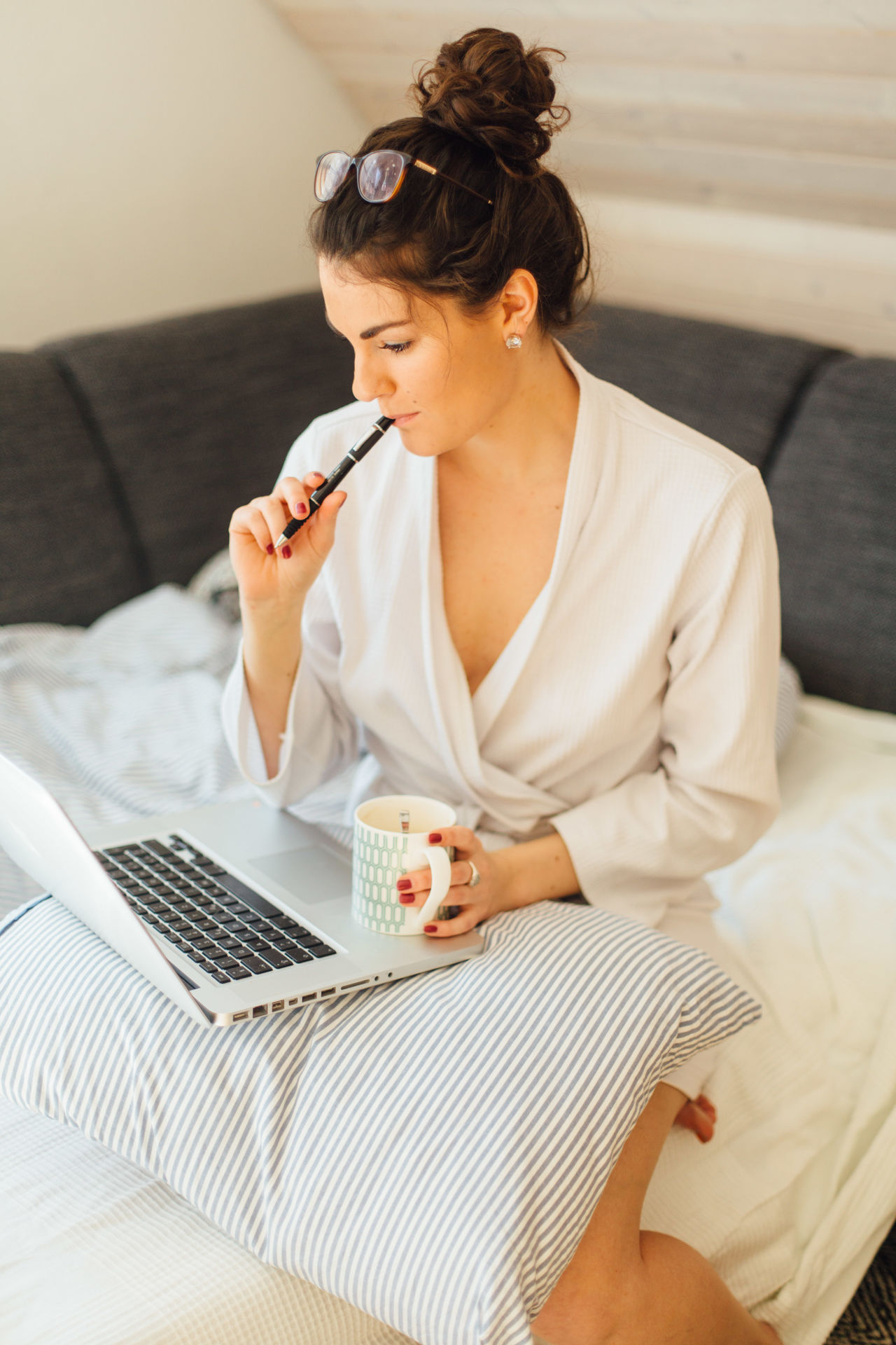 Young woman holding coffee cup using laptop while sitting on bed at home