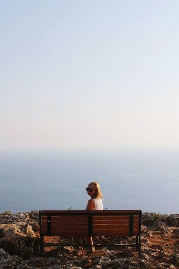 Woman Sitting On Bench At Cliff By Sea Against Clear Sky