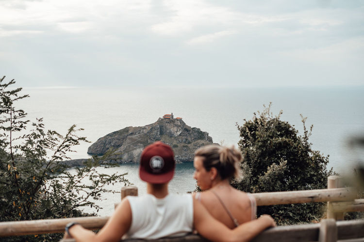 Rear view of couple sitting on bench against sea and sky