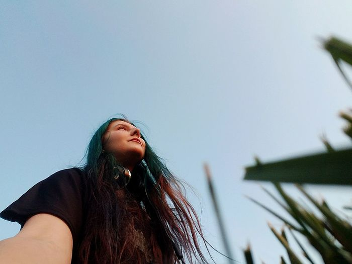 Low angle view of young woman against clear sky