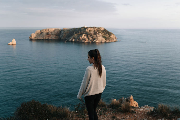 Woman standing on rock looking at sea against sky with island