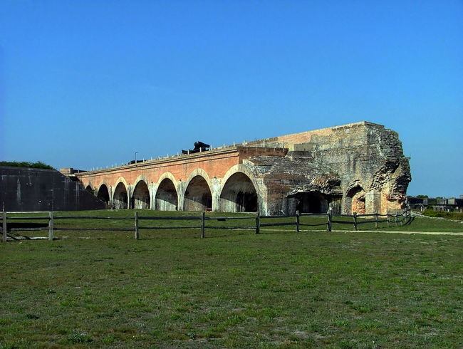View of the large arches supporting the weight of the fort Ancient Arch Architectural Column Architecture Blue Built Structure Clear Sky Day Exterior Façade Florida Travel Fort Pickens Grass Grassy Green Color History Lawn Nature No People Outdoors Sky The Past Tourism Travel Destinations