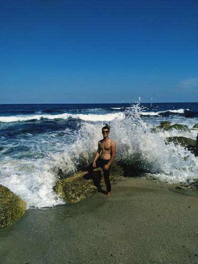 Full length of shirtless man on beach against clear sky