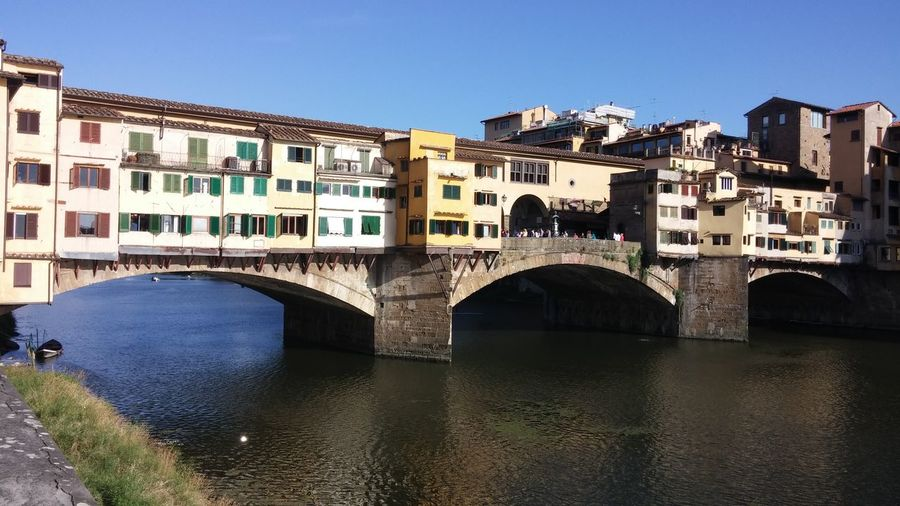 A bridge of beautiful old houses in Florence Toscana Arch Arch Bridge Architecture Blue Bridge Bridge - Man Made Structure Building Building Exterior Built Structure City Clear Sky Colorful Houses Connection House House On River Nature No People Old Buildings Outdoors River Sky Transportation Water Waterfront