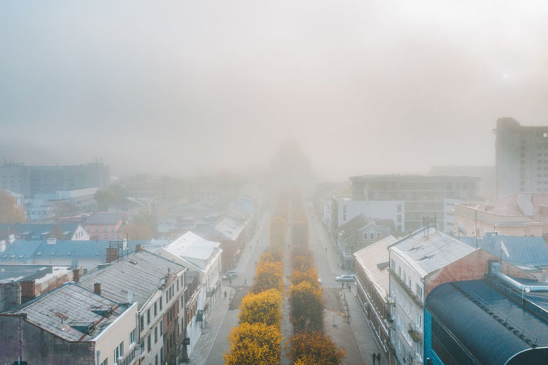 Aerial view of buildings amidst fog in city
