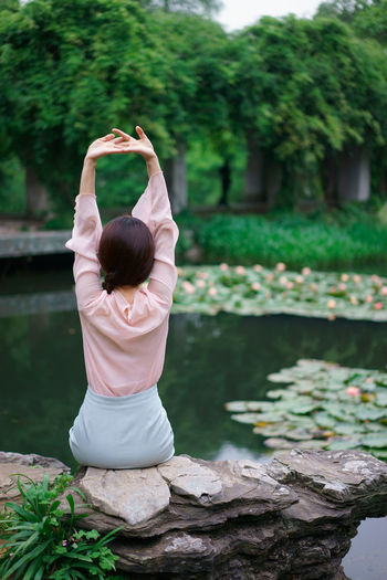 Rear view of woman with arms raised sitting on rock by lake at park