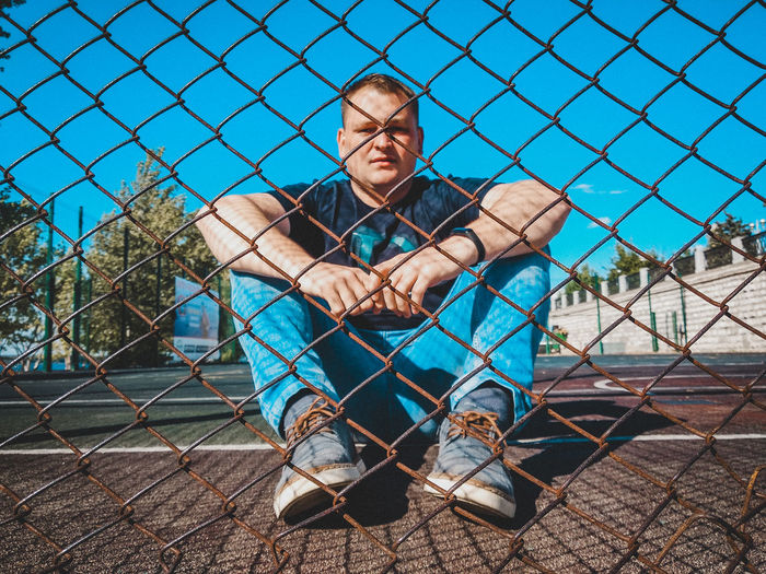 Portrait of man sitting seen through chainlink fence