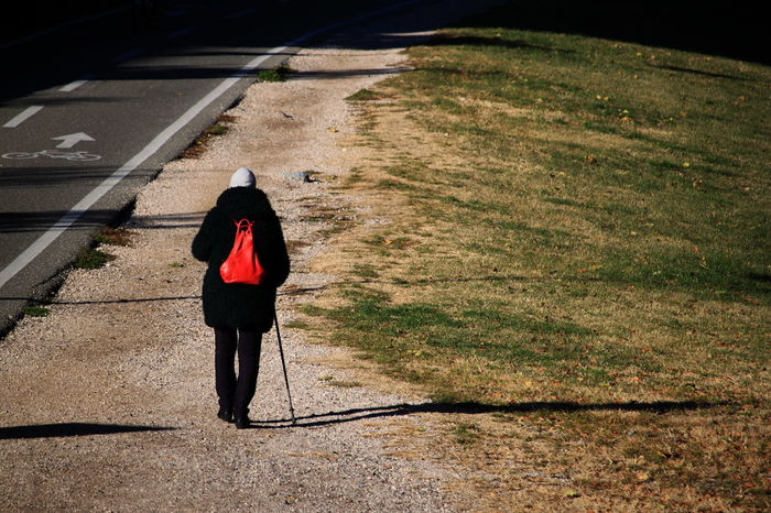 Walking Stick Woman Black Suit Bozen Bycicle Road Cap Day Full Length Grass November 2017 One Person Outdoors Real People Rear View Red Backpack Shadow Sunlight Walking