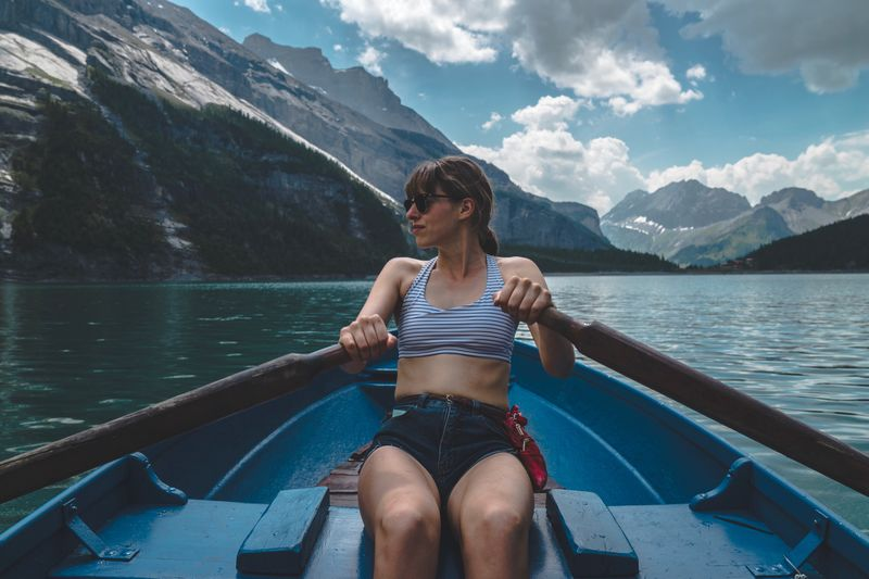 Young woman sitting on boat sailing in sea against mountains