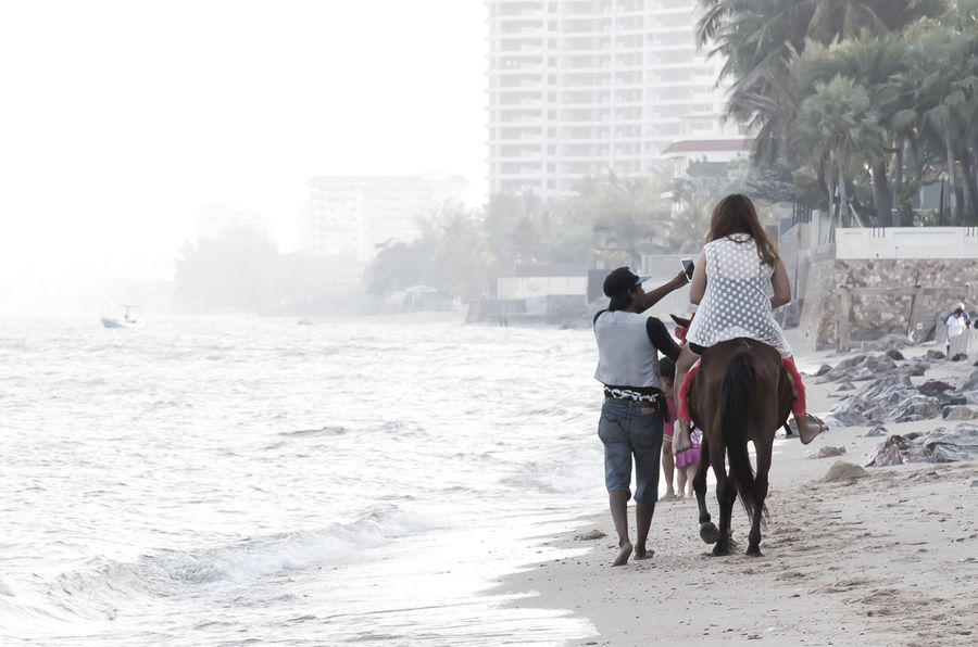Adult Animal Themes Architecture Beach Building Exterior Built Structure Day Domestic Animals Full Length Horse Riding Mammal Nature Outdoors People Real People Rear View Resort Hotel Seascape Thailand Togetherness Travel Destinations Tropical Paradise Two People Walking Waves, Ocean, Nature