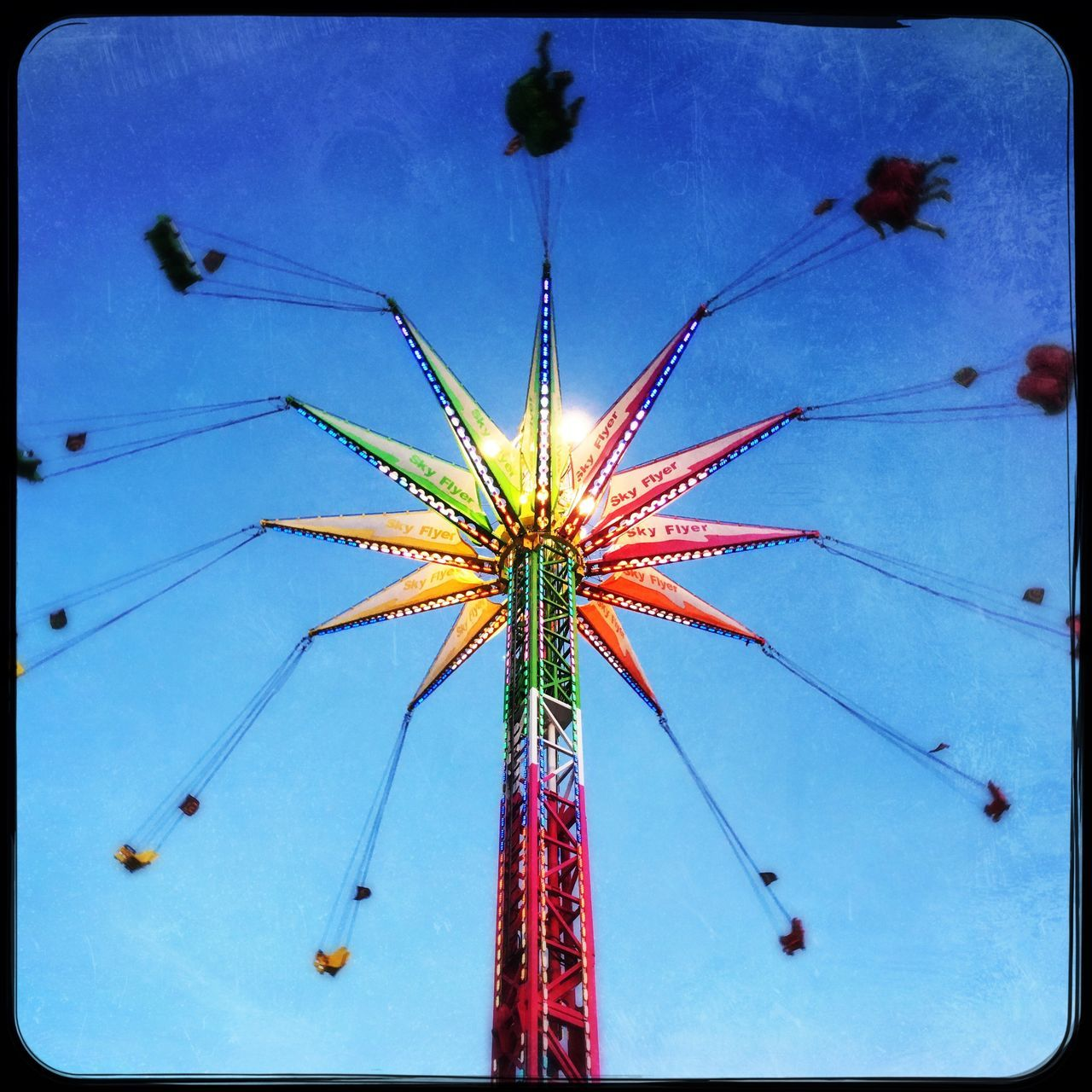 arts culture and entertainment, amusement park, low angle view, amusement park ride, blue, sky, outdoors, night, motion, no people, illuminated, clear sky