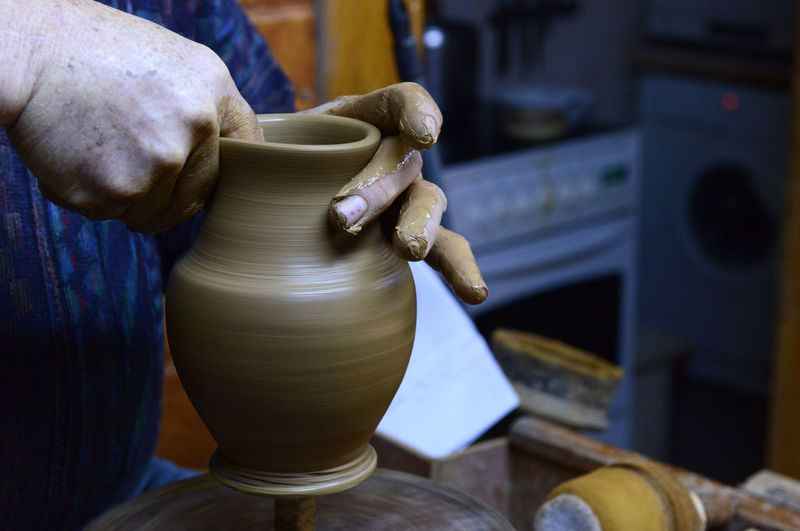 Craftsperson Shaping Pot On Pottery Wheel In Workshop