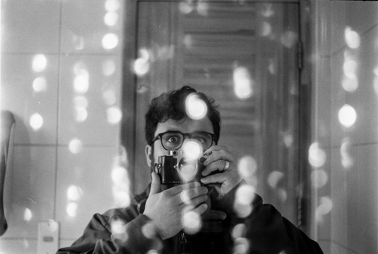 Portrait of man holding camera reflecting in mirror