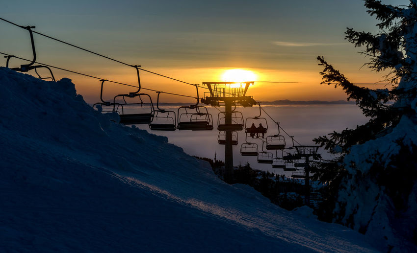 Chair ski lift with skiers at sunset Silhouette Ski Lift Skiing Beauty In Nature Cold Temperature Day Nature No People Orange Color Outdoors Scenics Sea Silhouette Sky Snow Sun Sunset Tranquil Scene Tranquility Transportation Winter