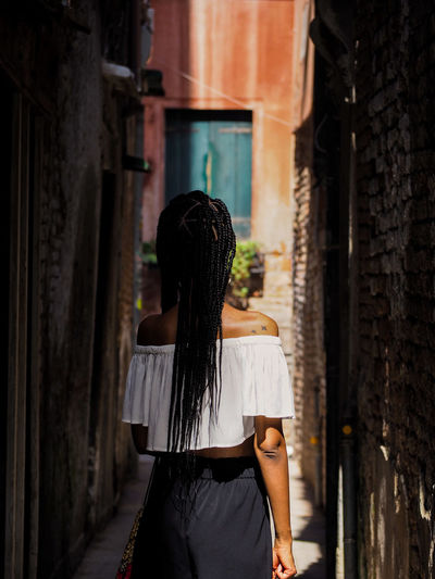Rear View Of Woman Standing In Alley