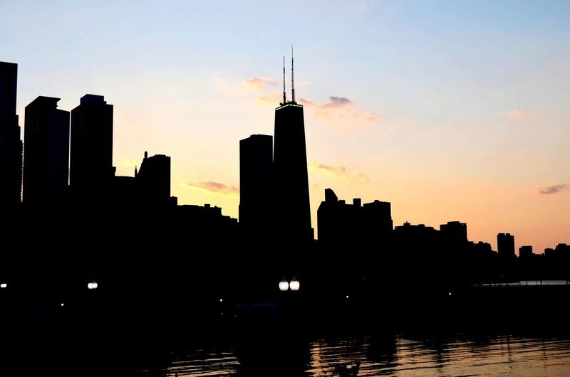 Silhouette of buildings in city at sunset