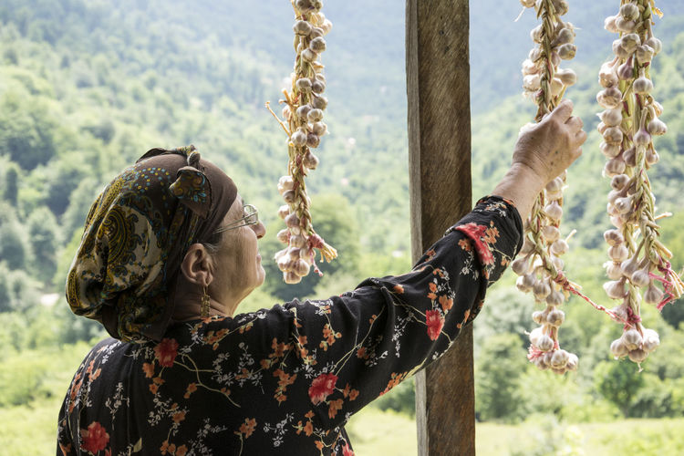 Rear view of woman hanging garlic cloves outdoors