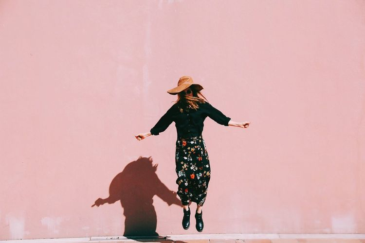 Woman jumping against pink wall