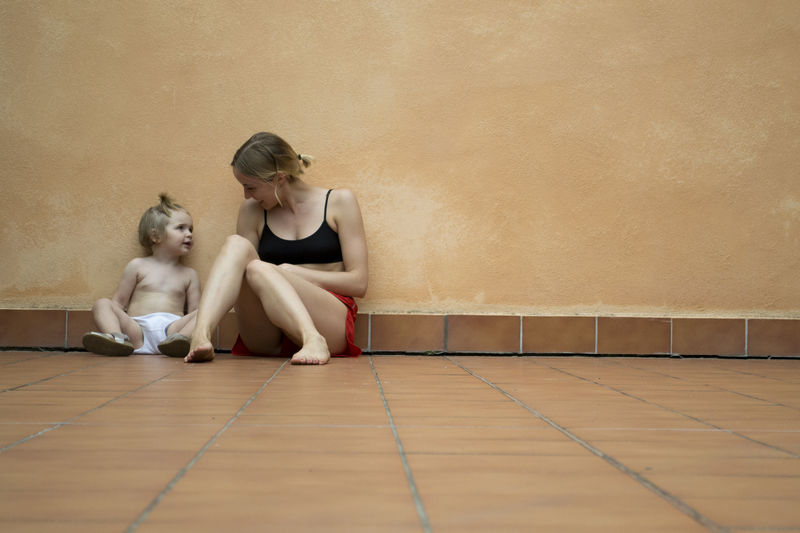 Smiling Woman Sitting With Daughter On Floor Against Wall