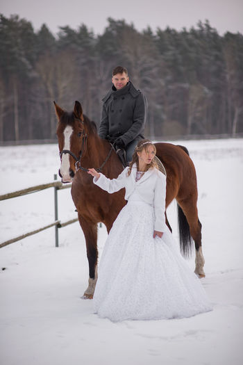 Portrait of smiling groom sitting on horse by bride on snow covered field