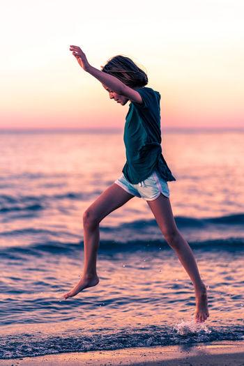 Full length of girl jumping on beach against sky during sunset