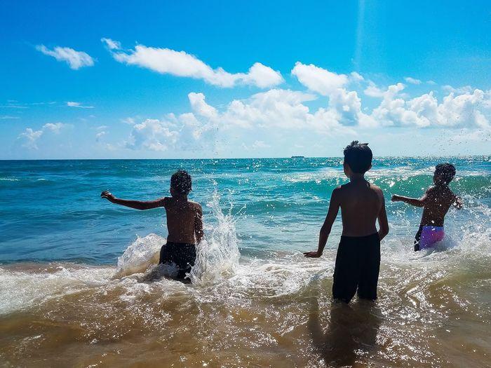 Boys in sea against sky