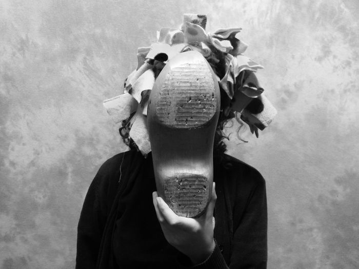 Woman hiding face with shoe against wall